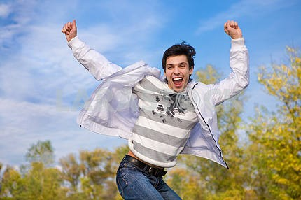 Happy young man jumps into air