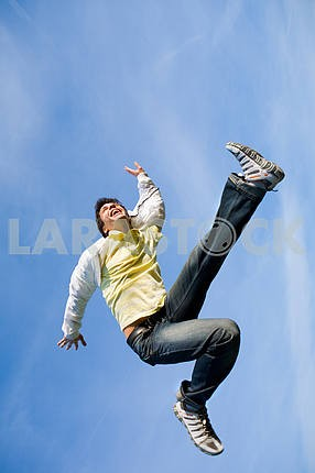 Happy young man - jumping  end flies in blue sky.