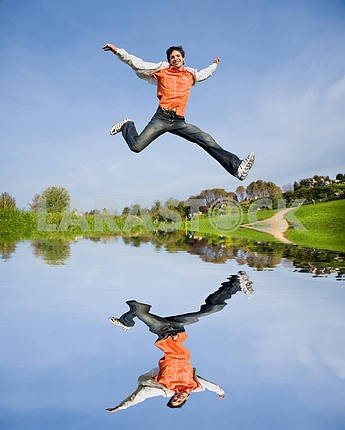 Happy young man - jumping  end fly in blue sky
