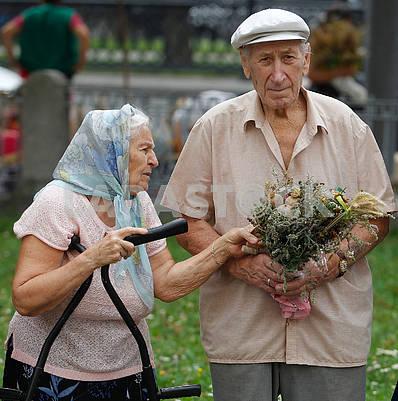 Пожилые люди с букетом