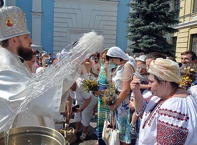 Priest sprinkles believers