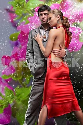 Красивая девушка в длинном красном платье держит экзотическим цветком в руке