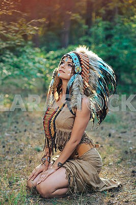 Young woman dressed in an Indian style in the woods  in the Indian roach with feathers