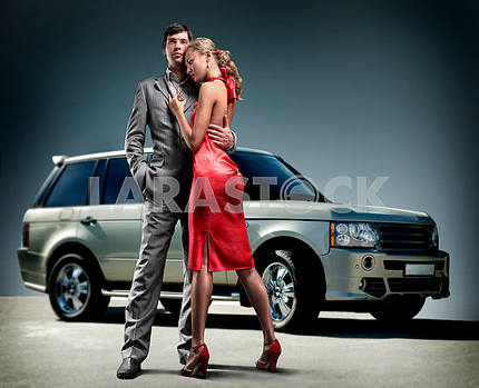 Young beautiful couple backdrop car
