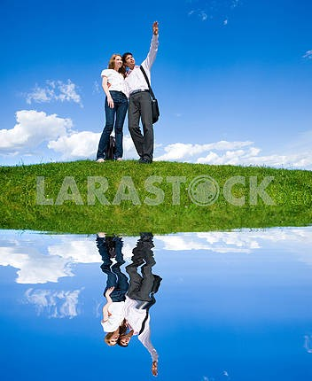 Happy young couple looking at something above a green meadow. Ma