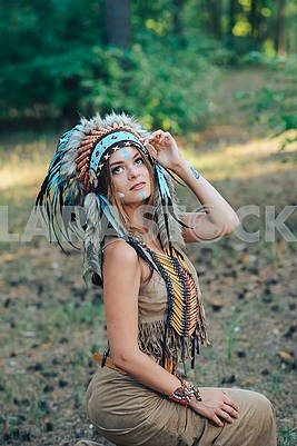 Young woman dressed in an Indian style in the woods Portrait of a young lady in the Indian roach Beautiful girl in a suit of the American Indian
