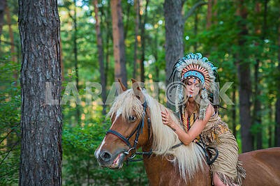 Beautiful girl in a suit of the American Indian riding a horse in the forrest