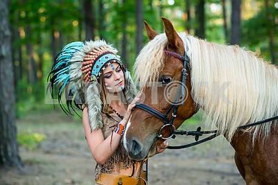 Красивая девушка в костюме индейской женщины в плотва с лошадью