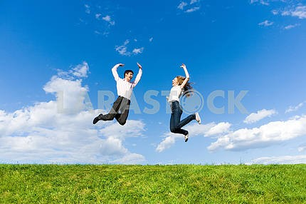 Happy Young Couple - team is jumping in the sky above a green me