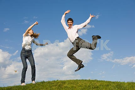 Happy smiling couple  jumping in blue sky