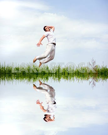 Happy man in white clothes is jumping over the grass near the la