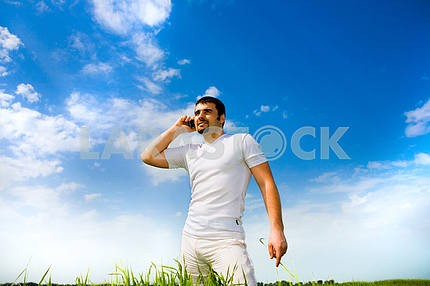 Man at the phone in the field under blue sky. In white dress