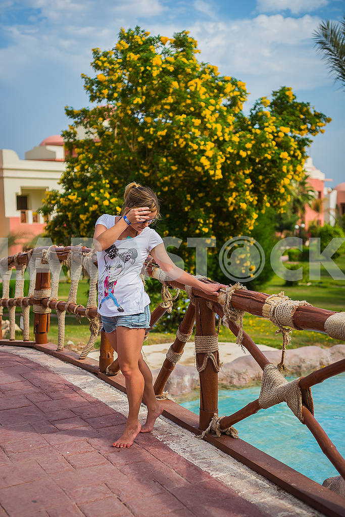 A young woman standing on the bridge near the pool. having rest in Egypt . green tree with the yellow  flowers on the background. travel — Image 62754