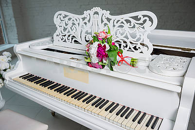 wedding bouquet on the  white grand piano - decoration for the wedding