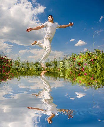 Happy young man is running in a field