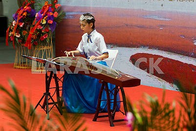 The girl is playing the instrument Zhenzhen