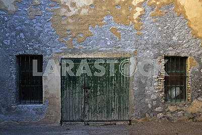 Old wooden gates and two grating windows