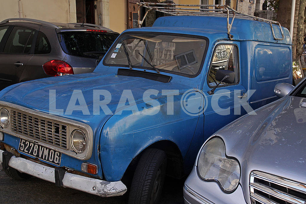 An old blue car between two new cars — Image 63194