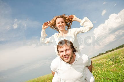 Young couple walking through summer lawn