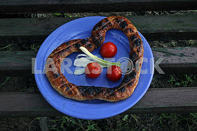 Grilled sausage in the form of heart and vegetables