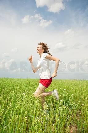 Happy young women runing in field
