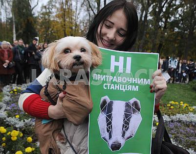 Девушка держит собаку и плакат