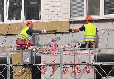 Workers insulate a dwelling house