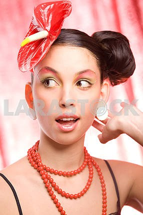 Trend model with a red flower on the head. Ideal skin. With a br