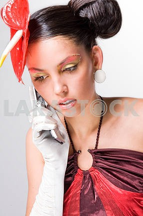 Girl with a red flower and in white gloves speaks by a mobile ph