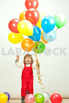 little girl in red jumping with balloons