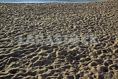 People trampled sand on the Mediterranean Sea beach in the morni
