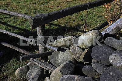 Большие овальные камни под забором
