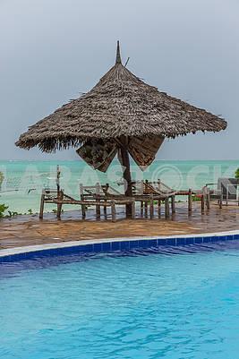 Соломенные зонты и шезлонги на пляже