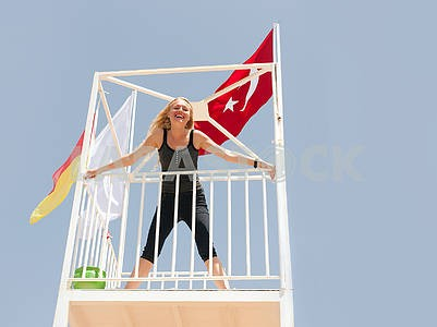 Cute blonde at the watchtower of lifeguards on the beach.