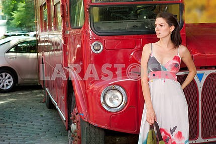 Beautiful girl in the background of a red bus