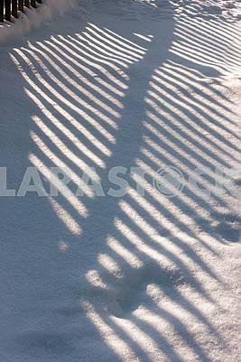 Забор тень на снег накопленной колоде