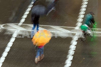 eople with umbrellas walking in the rain