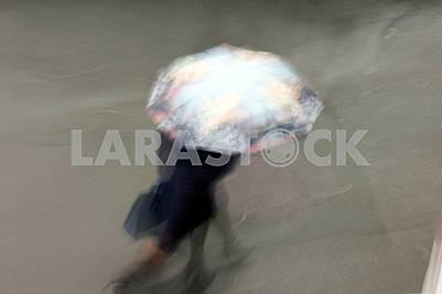 Эопл с зонтиками, идущими под дождем