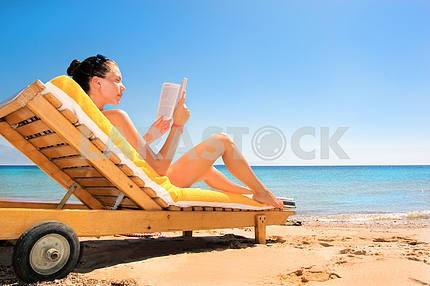Beautiful woman reading a book on beach