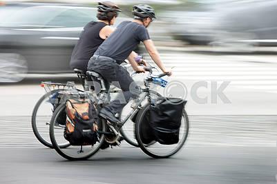 Люди на велосипедах в движении размываются на проезжей части города