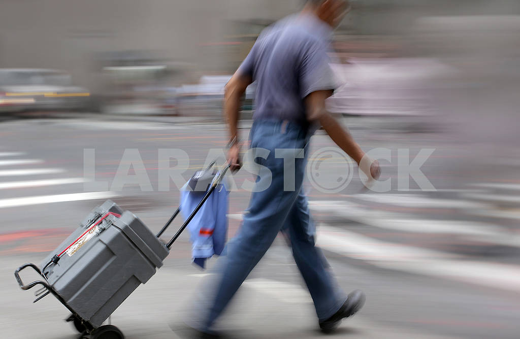 A man with luggage trolley walking down the street — Image 65277