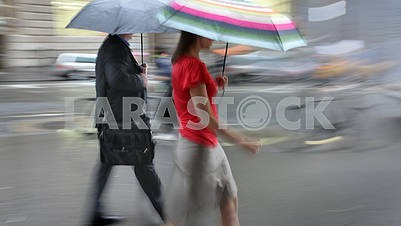 Man and woman with umbrellas walking on the street