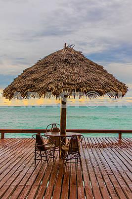 Соломенный зонт, стол и стулья