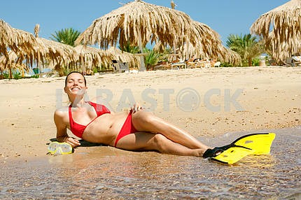 Girl in a red bikini with a mask and flippers on the beach