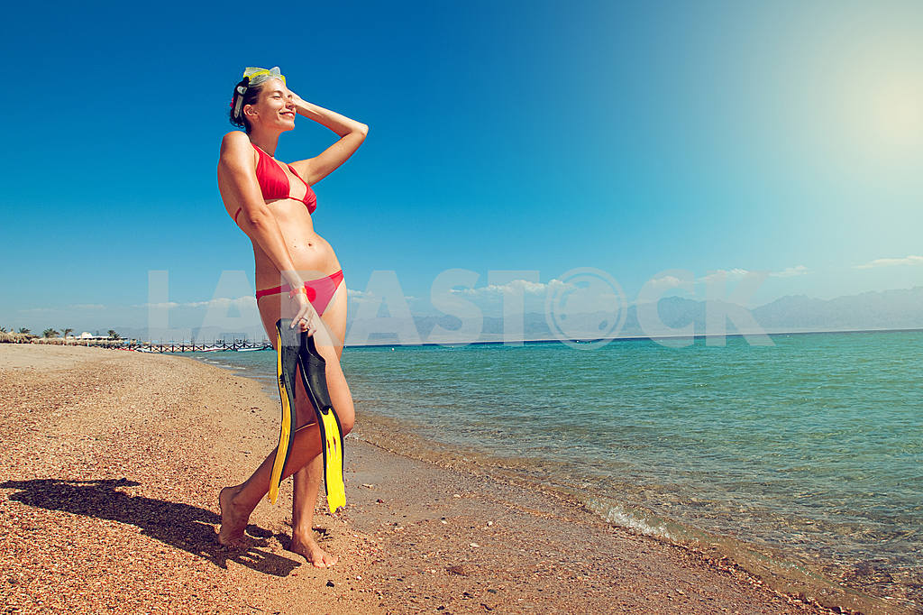 Girl in a red bikini with a mask and flippers on beach — Image 6554