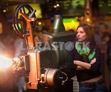 girl looks at an old movie projector