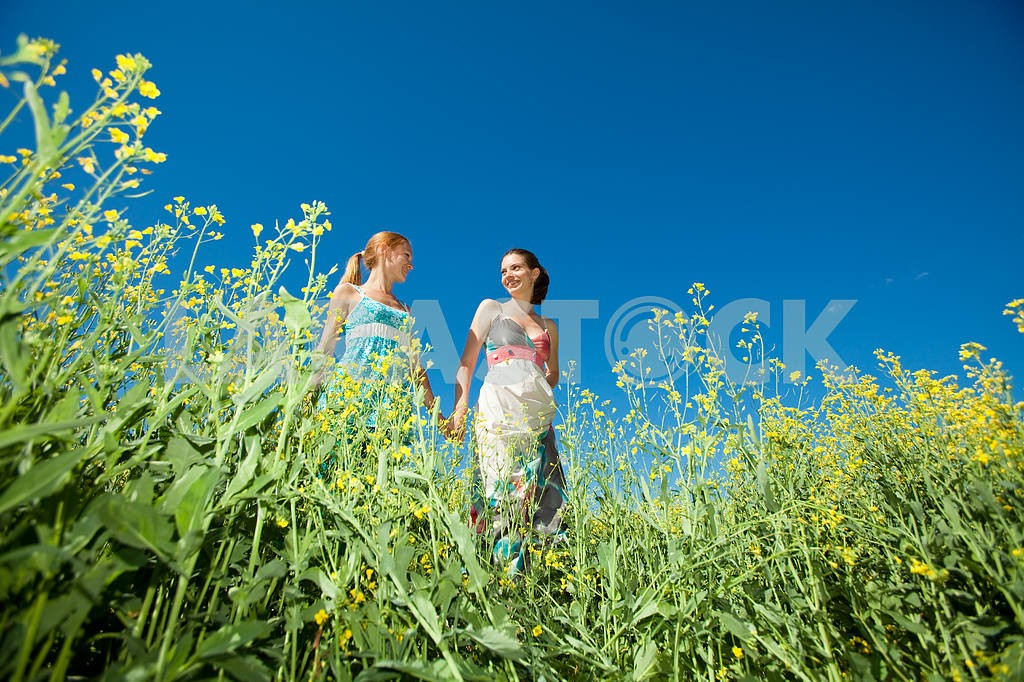 Two beautiful girl in white clothes go to the yellow flowers — Image 6660