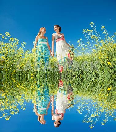 Две красивые девушки в белых одеждах идут на желтых цветов