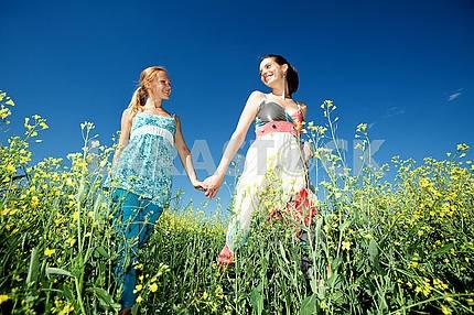 Two girlfriends having fun in blue sky