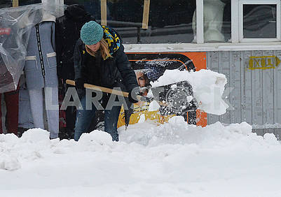 A woman cleans the street of snow